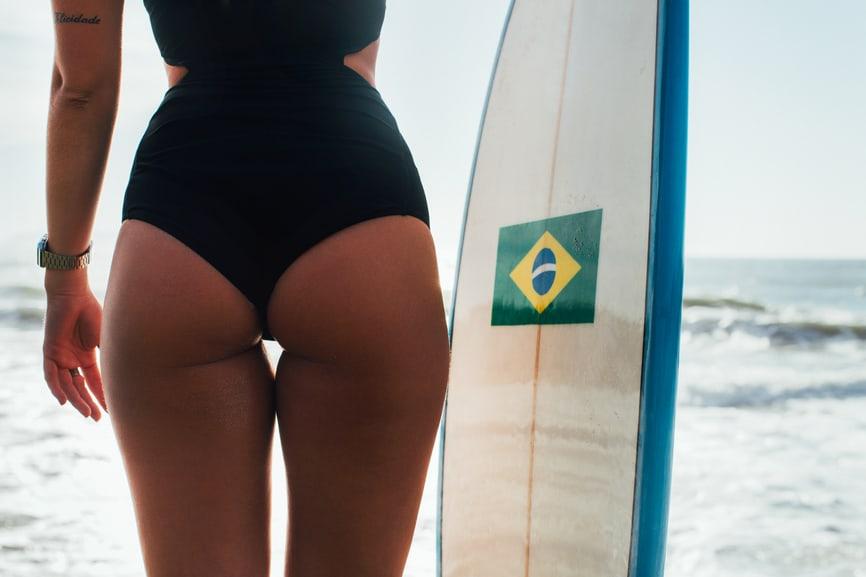 Bum Of Hot Female Surfer Girl Posing With Surfboard On Ipanema Beach In Rio De Janeiro